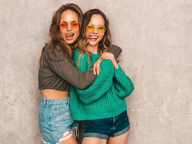 Twee jonge mooie lachende prachtige meisjes in trendy zomerkleren. sexy zorgeloze vrouwen poseren. positieve modellen met plezier in ronde zonnebril. tong tonen