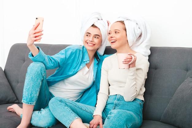 Twee jonge mooie lachende vrouwen zitten op de bank. zorgeloze modellen poseren binnenshuis in een chique appartement of hotelkamer