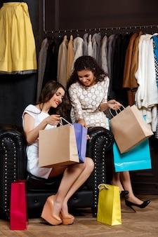 Twee jonge mooie meisjes die aankopen in winkelcomplex bekijken.