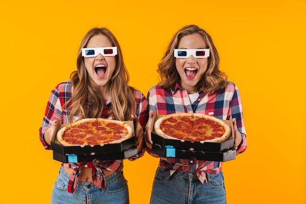 Twee jonge mooie meisjes die een 3d-bril dragen die pizzadozen geïsoleerd houden