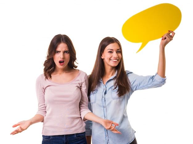 Twee jonge mooie meisjes die gele bel voor tekst houden.