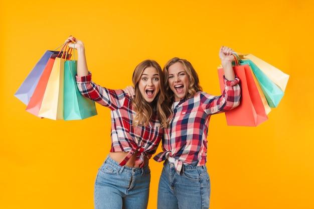 Twee jonge mooie meisjes die geruite overhemden dragen die glimlachen en kleurrijke boodschappentassen geïsoleerd houden