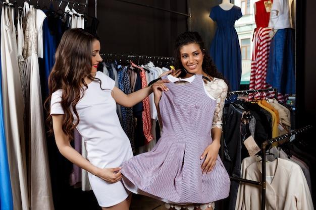 Twee jonge mooie meisjes die in wandelgalerij winkelen.
