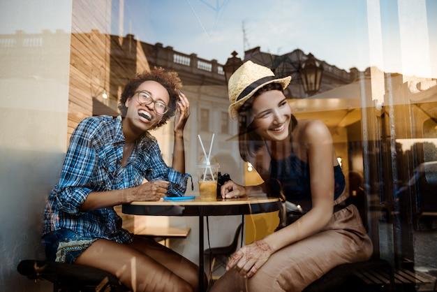 Twee jonge mooie meisjes glimlachen, lachen, rusten in cafe. schot van buitenaf.
