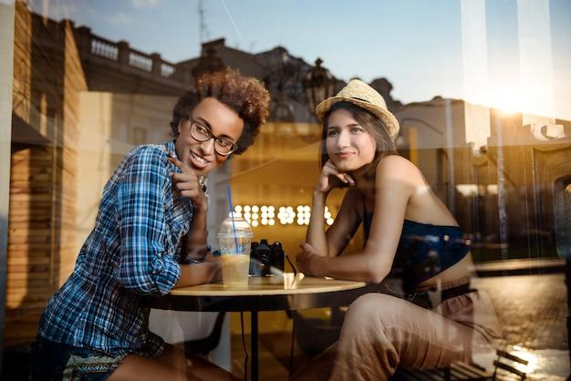 Twee jonge mooie meisjes glimlachen, spreken, die in koffie rusten. schot van buitenaf.