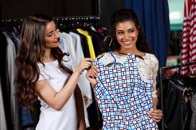 Twee jonge mooie meisjes maken winkelen in winkelcentrum.
