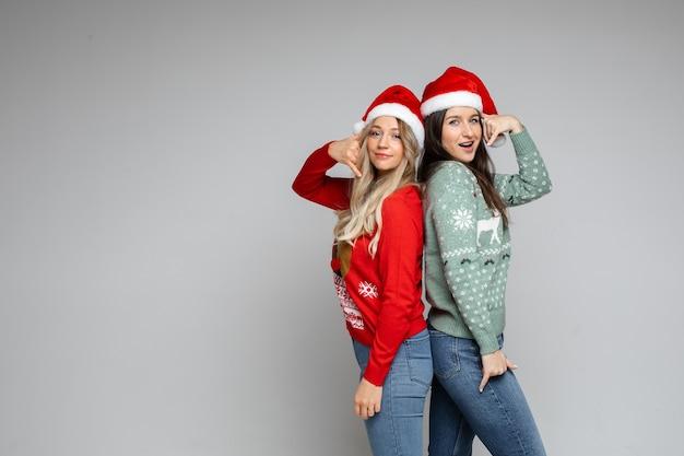 Twee jonge mooie meisjes met kerstmuts tonen bel me gebaar op grijze achtergrond met kopieerruimte