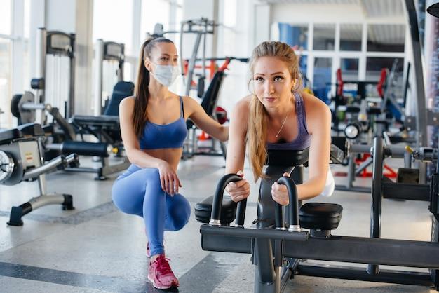 Twee jonge mooie meisjes oefenen in de sportschool met maskers tijdens de pandemie