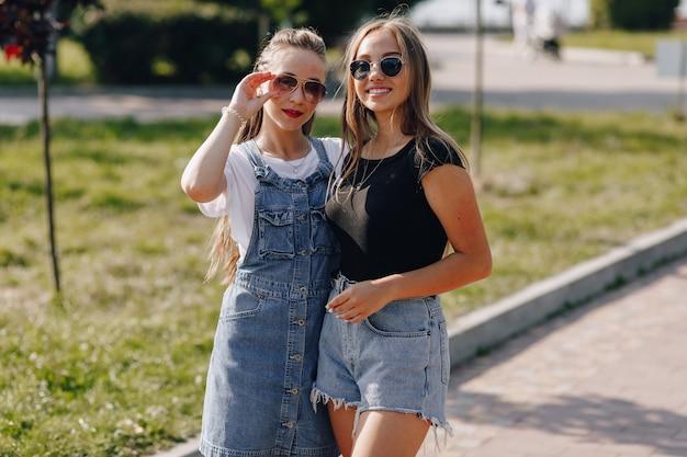 Twee jonge mooie meisjes op een wandeling in het park. een zonnige zomerdag, vreugde en vriendschappen.