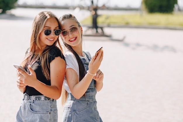 Twee jonge mooie meisjes op een wandeling in het park met telefoons. zonnige zomerdag, vreugde en vriendschappen.