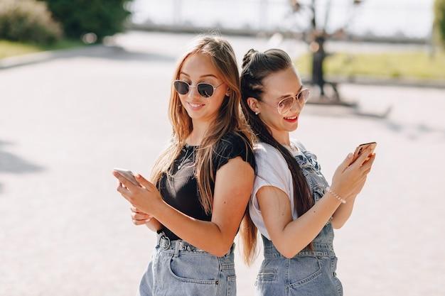 Twee jonge mooie meisjes op een wandeling in het park met telefoons