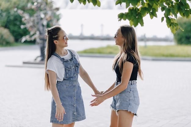 Twee jonge mooie meisjes op een wandeling in het park of op straat