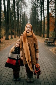 Twee jonge mooie meisjes poseren in het park