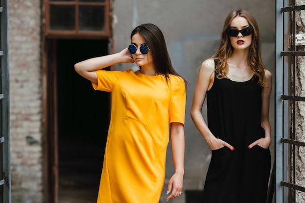 Twee jonge mooie meisjes poseren tegen een verlaten gebouw