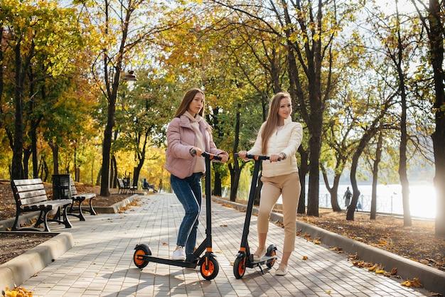 Twee jonge mooie meisjes rijden elektrische scooters in het park op een warme herfstdag.