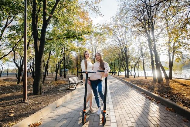 Twee jonge mooie meisjes rijden elektrische scooters in het park op een warme herfstdag
