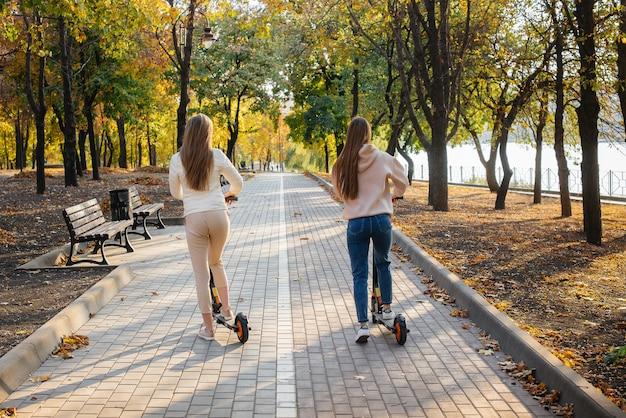 Twee jonge mooie meisjes rijden op elektrische scooters in het park op een warme herfstdag.