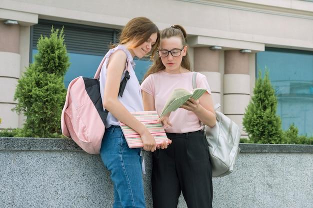 Twee jonge mooie meisjes studenten met rugzakken, boeken