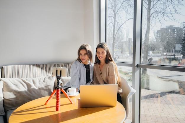 Twee jonge mooie meisjes zitten in een café, nemen videoblogs op en communiceren op sociale netwerken.