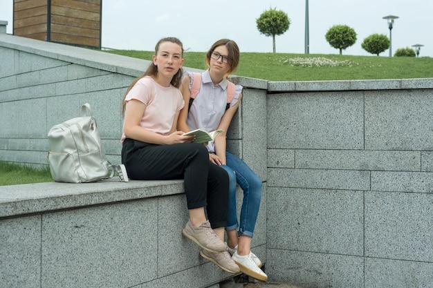 Twee jonge mooie meisjesstudenten met rugzakken, boeken