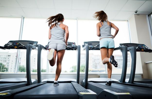 Twee jonge mooie slanke vrouwen in sportkleding draait op loopbanden in de sportschool met ramen en stad op de achtergrond