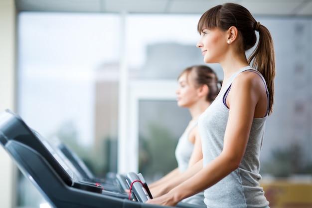 Twee jonge mooie slanke vrouwen in sportkleding staande op loopbanden in de sportschool