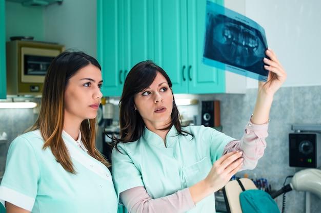 Twee jonge mooie tandartsen die samenwerken