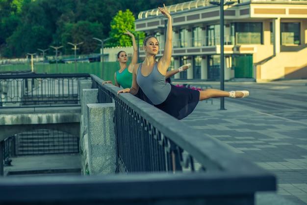 Twee jonge mooie tweelingzus dansen ballet in de stad met ballet kostuum urban sync dance