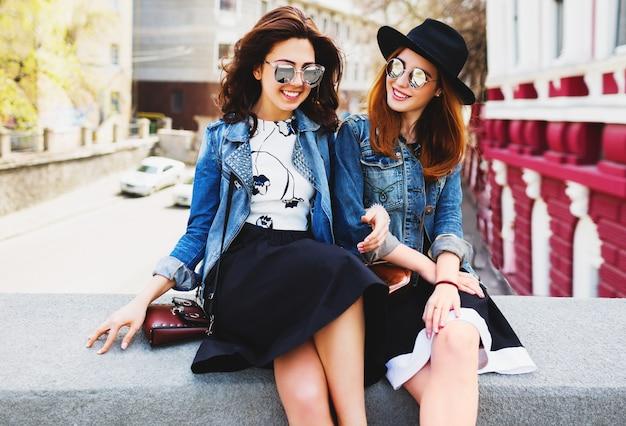 Twee jonge mooie vriendenvrouwen die plezier hebben buiten op straat