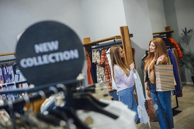 Twee jonge mooie vriendinnen winkelen nieuwe collectie in de moderne winkel