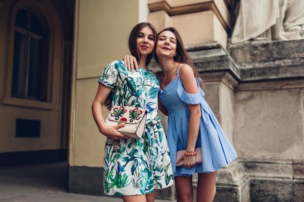 Twee jonge mooie vrouwen die in openlucht koesteren. meisjes met plezier in de stad. beste vrienden hangen rond