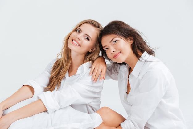 Twee jonge mooie vrouwen die op wit bed zitten en camera bekijken
