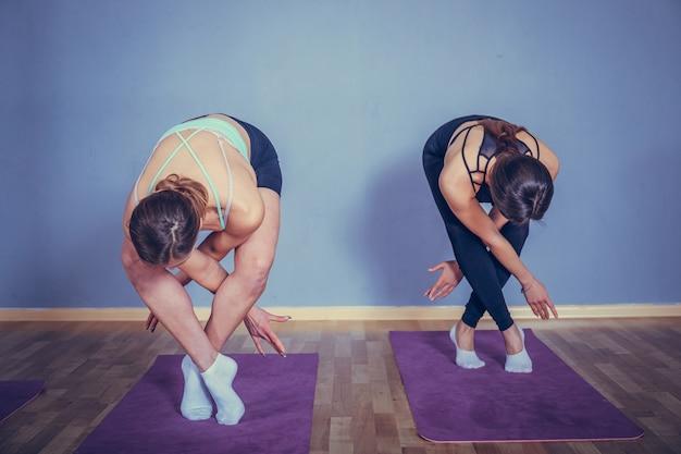 Twee jonge mooie vrouwen doen yoga asana uitgebreide zijhoek vormen.