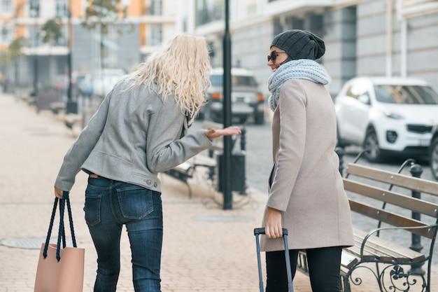 Twee jonge mooie vrouwen in warme kleren lopen