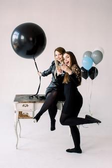 Twee jonge mooie vrouwen in zwarte jurken houden lucht ballonnen bij elkaar, het vieren van kip of verjaardagsfeestje in de buurt van de vintage witte tafel met kasten, geïsoleerd op wit
