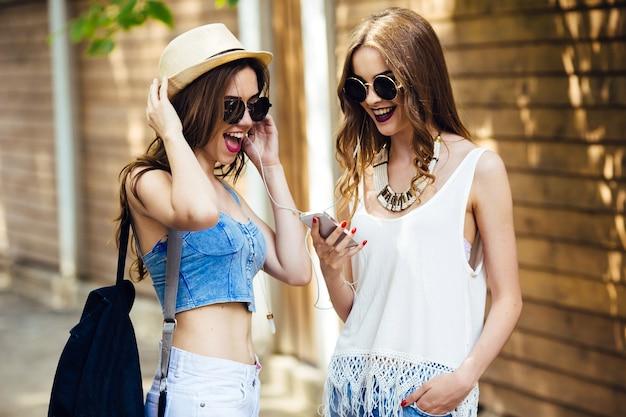 Twee jonge mooie vrouwen lopen door de stad en luisteren naar muziek