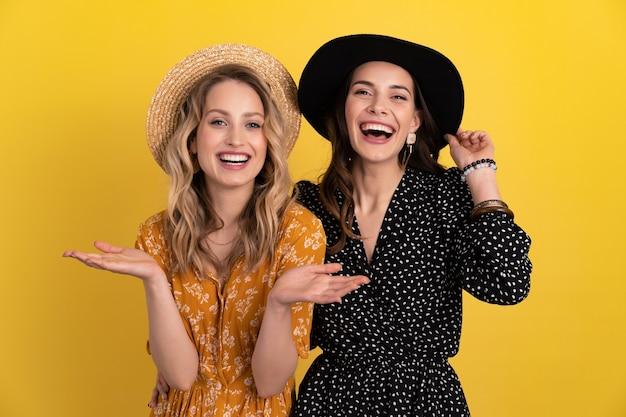 Twee jonge mooie vrouwen vrienden samen geïsoleerd op geel in zwarte en gele jurk en hoed stijlvolle boho trend