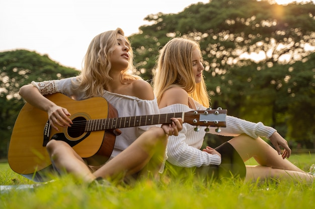 Twee jonge mooie vrouwenvrienden die in openlucht een gitaar spelen en in park met zonsondergang zingen.