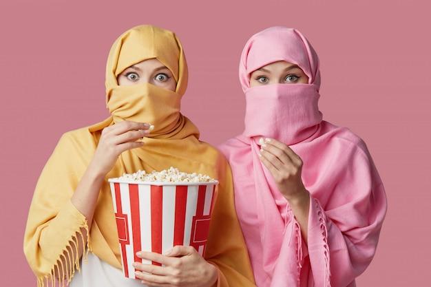Twee jonge moslim arabische vrouwen dragen kleurrijke hijaabs tegen roze muur