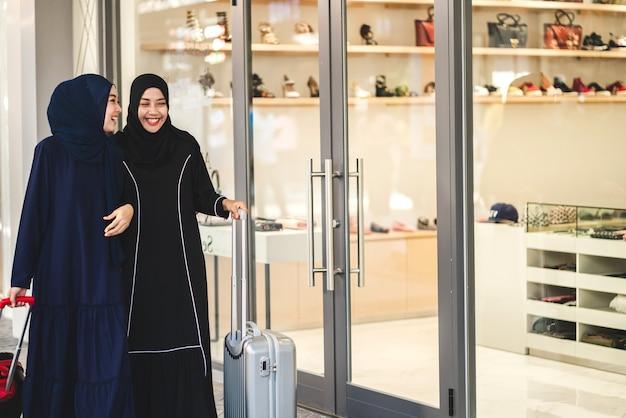Twee jonge moslimvrouwen die genieten van winkelen en plezier maken