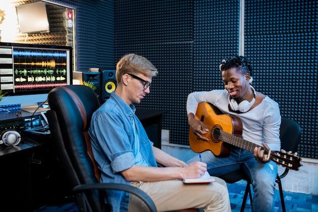 Twee jonge multiculturele mannen gitaarspelen en notities maken in kladblok terwijl ze liedjes maken in geluidsopnamestudio