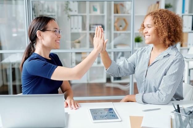 Twee jonge multiculturele office managers of bankiers geven elkaar een high five na het werk over een nieuw project of presentatie