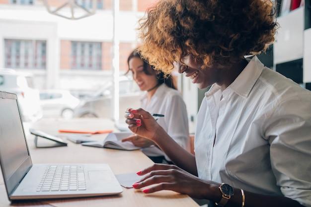 Twee jonge multiraciale vrouwen die samen aan een project schrijven werken