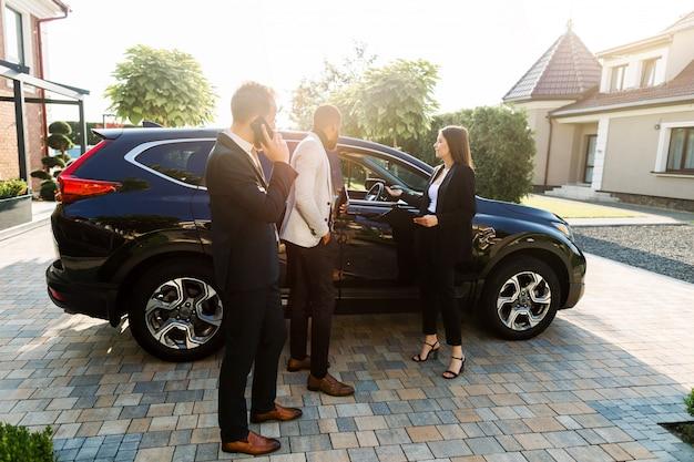 Twee jonge multiraciale zakenlieden, afrikaans en kaukasisch, die een nieuwe auto kiezen die zich met verkoper, jonge mooie vrouw bevinden, in de autoshowroom in openlucht. zijaanzicht