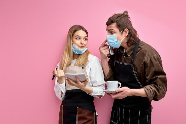 Twee jonge obers in schort en masker bespreken bestellingen, klaar om klanten te bedienen tijdens quarantaine