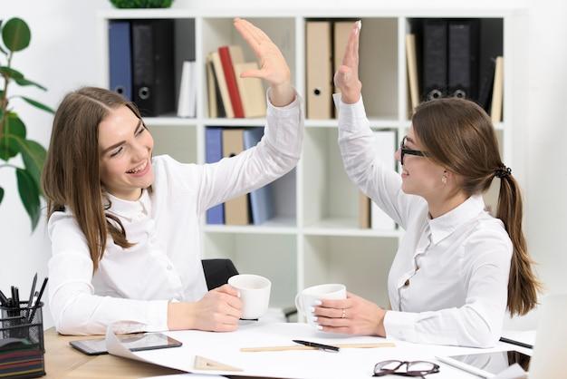 Twee jonge onderneemsters die elkaar bekijken die hoogte vijf aan elkaar in het bureau geven
