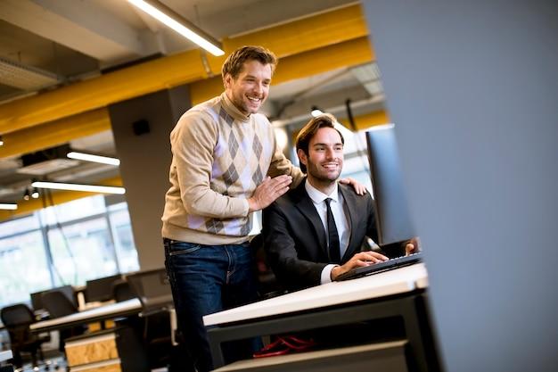 Twee jonge ondernemers bespreken in kantoor bij de tafel