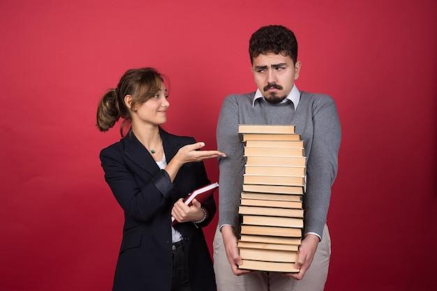 Twee jonge ondernemers met boeken die elkaar aanstaren
