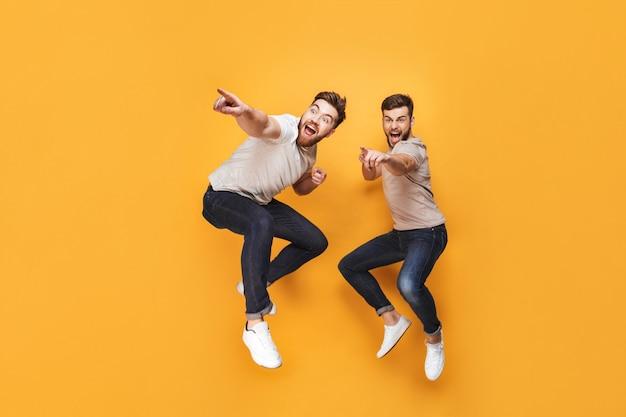 Twee jonge opgewonden mannen die samen springen