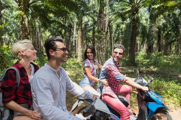 Twee jonge paren maken reis door scooter gelukkig mensen reizen